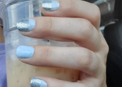hand holding iced drink with blue and silver nails
